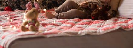 Ein kleines Kind liegt auf einem Bett mit einem Elch nahe einem Baum des neuen Jahres, hält ein Telefon, eine Tablette Snowy-Wint lizenzfreies stockbild