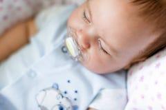 Ein kleines Kind schläft mit einem Friedensstifter, Abschluss oben stockbilder