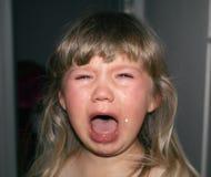 Ein kleines Kind schreit mit Rissen und geifert Kind-` s Hysterie Stockbild