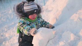 Ein kleines Kind spielt in einem Winter Park mit Schnee Ein sonniger Wintertag Spaß und Spiele in der Frischluft Stockfoto