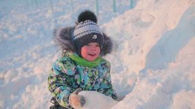 Ein kleines Kind spielt in einem Winter Park mit Schnee Ein sonniger Wintertag Spaß und Spiele in der Frischluft Lizenzfreie Stockfotografie
