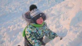 Ein kleines Kind spielt in einem Winter Park mit Schnee Ein sonniger Wintertag Spaß und Spiele in der Frischluft stockbilder
