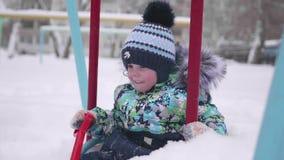 Ein kleines Kind spielt in Winter Park Ein Kind auf einem Schwingen Ein sonniger Wintertag Spaß und Spiele in der Frischluft stock video footage