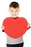 Ein kleines Kind steht und hält das Herz Stockfotografie