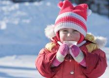 Ein kleines Kind trinkt ein heißes Getränk im Winter stockbild