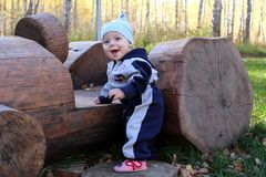 Ein kleines Kind zu den hölzernen Klotz eines lächelnden Sommers mit hölzerner Maschine im Park stockfotos
