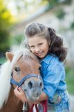 Ein kleines lächelndes Mädchen mit dem gelockten Haar kleidete in den Jeans gehend mit einem Pony am Stall an lizenzfreie stockfotografie