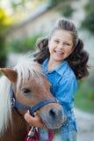 Ein kleines lächelndes Mädchen mit dem gelockten Haar kleidete in den Jeans gehend mit einem Pony am Stall an stockbilder
