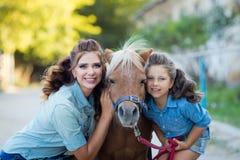 Ein kleines lächelndes Mädchen mit einem netten Pony mit dem gelockten Haar der Mutter kleidete in den Jeans gehend am Stall an stockfotografie