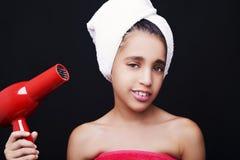 Ein kleines lächelndes Mädchen mit einem Tuch auf ihrem Kopf und Haartrockner Stockbild