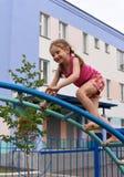 Ein kleines lächelndes Mädchen, welches die Sportausrüstung in einem Spielplatz eines Wohnung house& x27 verwendet; s-Vorhof stockfoto