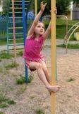 Ein kleines lächelndes Mädchen, welches die Sportausrüstung in einem Spielplatz eines Wohnung house& x27 verwendet; s-Vorhof stockbild