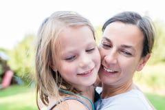 Ein kleines lachendes Mädchen in den Armen ihrer Mutter, die ihre Wünsche während einer Geburtstagsfeier im Garten macht stockbilder