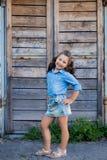 Ein kleines lachendes Mädchen mit dem gelockten Haar kleidete in den Jeans mit am Stall nahe der Holztür an lizenzfreie stockfotografie