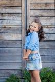 Ein kleines lachendes Mädchen mit dem gelockten Haar kleidete in den Jeans mit am Stall nahe der Holztür an lizenzfreie stockbilder