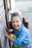 Ein kleines lachendes Mädchen mit dem gelockten Haar kleidete in den Jeans mit am Stall nahe der Holztür an stockfotografie