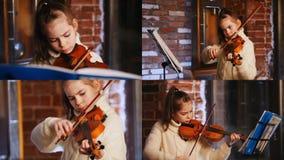4 in 1 Ein kleines Mädchen in der weißen Strickjacke, die Violine durch Anmerkungen spielt stock video