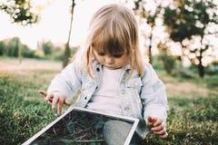 Ein kleines Mädchen auf dem Gras Lizenzfreies Stockfoto
