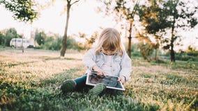 Ein kleines Mädchen auf dem Gras Stockfotos