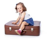 Ein kleines Mädchen auf dem Koffer Stockbilder
