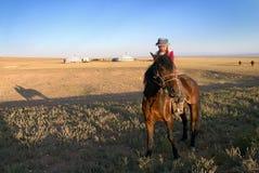 Ein kleines Mädchen auf einem Pferd in der mongolischen Steppe Lizenzfreies Stockbild