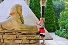 Ein kleines Mädchen betrachtet die alte Parknachahmung von ägyptischen Anziehungskräften stockfotos