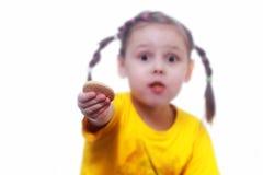 Ein kleines Mädchen bietet einen Biskuit an lizenzfreies stockbild