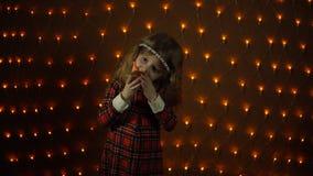 Ein kleines Mädchen brennt heraus eine Kerze durch und beißt ihren Geburtstagskuchen stock footage