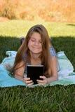 Ein kleines Mädchen, das auf dem Gras mit ihrer Tablette liegt stockfotos
