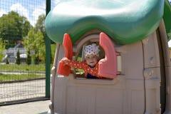 Ein kleines Mädchen, das auf dem Spielplatz, Blicke aus dem Waisenhaus heraus spielt lizenzfreie stockfotografie