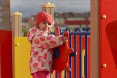 Ein kleines Mädchen, das auf dem Spielplatz im goldenen Herbst spielt stockbilder