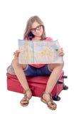 Ein kleines Mädchen, das auf einem Koffer sitzt und a liest Lizenzfreies Stockfoto