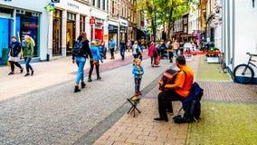 Ein kleines Mädchen, das auf einen Busker spielt das Akkordeon im beschäftigten Diezerstraat in der Mitte der historischen Stadt  lizenzfreie stockfotos