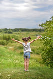 Ein kleines Mädchen, das auf einer grünen Ferse zurück zu dem Zuschauer mit ihren Händen oben sitzt und vortäuscht, die Welt zu u Lizenzfreies Stockfoto