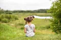 Ein kleines Mädchen, das auf einer grünen Ferse zurück zu dem Zuschauer sitzt und eine malerische Landschaft beobachtet Lizenzfreies Stockbild