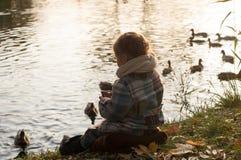 Ein kleines Mädchen, das auf einer Seeseite, die Wasser- und Fütterungsenten betrachtend sitzt Stockbild