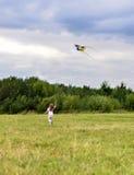 Ein kleines Mädchen, das auf grünem Gras den hellen Fliegendrachen nachläuft Stockfotos