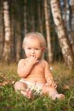 Ein kleines Mädchen, das auf grünem Gras sitzt Stockfotografie