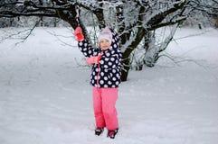 Ein kleines Mädchen, das auf Schnee im Winterpark sitzt stockfotografie