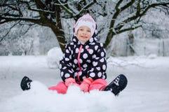 Ein kleines Mädchen, das auf Schnee im Winterpark sitzt lizenzfreie stockfotos