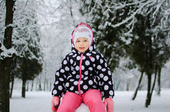 Ein kleines Mädchen, das auf Schnee im Winterpark sitzt stockfotos