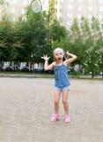 Ein kleines Mädchen, das Badminton in einem Yard einer buiding Wohnung spielt Lizenzfreies Stockbild