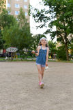 Ein kleines Mädchen, das Badminton in einem Yard einer buiding Wohnung spielt Stockfoto