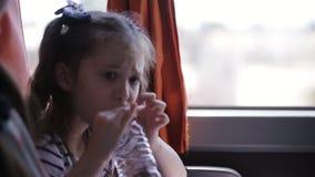 Ein kleines Mädchen, das in Bus reisen und Getränke wässern von einer Plastikflasche stock video footage