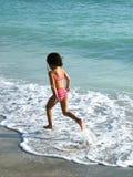 Ein kleines Mädchen, das in das Meer springt Lizenzfreie Stockfotos