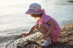 Kleines Mädchen, das nahe dem Wasser sitzt Stockbilder