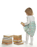 Ein kleines Mädchen, das ein großes Buch anhebt Stockbild