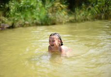 Ein kleines Mädchen, das in einem See spielt Stockfoto
