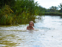 Ein kleines Mädchen, das in einem See spielt Lizenzfreie Stockfotos