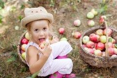 Ein kleines Mädchen, das einen Apfel im Garten isst Lizenzfreie Stockfotos